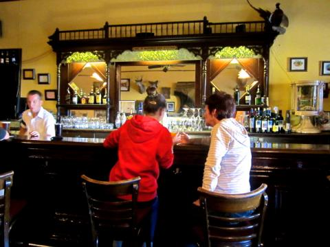 Photo : Barman et 2 jeunes femmes assise au bar d'un saloon